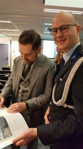 Illustratie van het zetten van de handtekening in het boek In een rechte lijn door staatssecretaris Klaas Dijkhoff