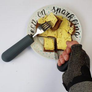 Foto van vork met handvatverdikker en het snijden met een hoekmes vanwege de ziekte van bechterew en spalken