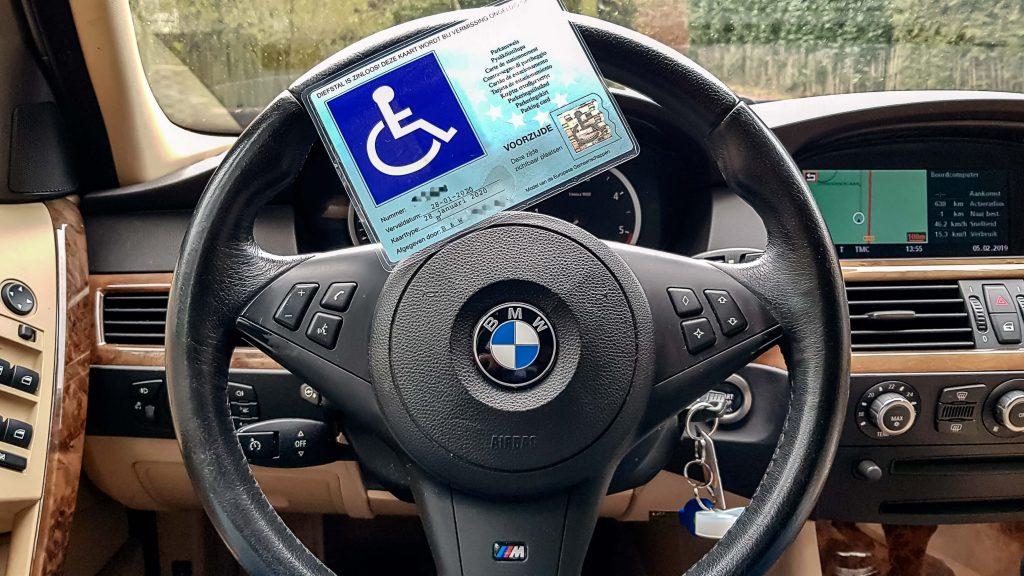 Afbeelding van gehandicaptenparkeerkaart vanwege ziekte van bechterew reuma op het stuur van een BMW 5-serie