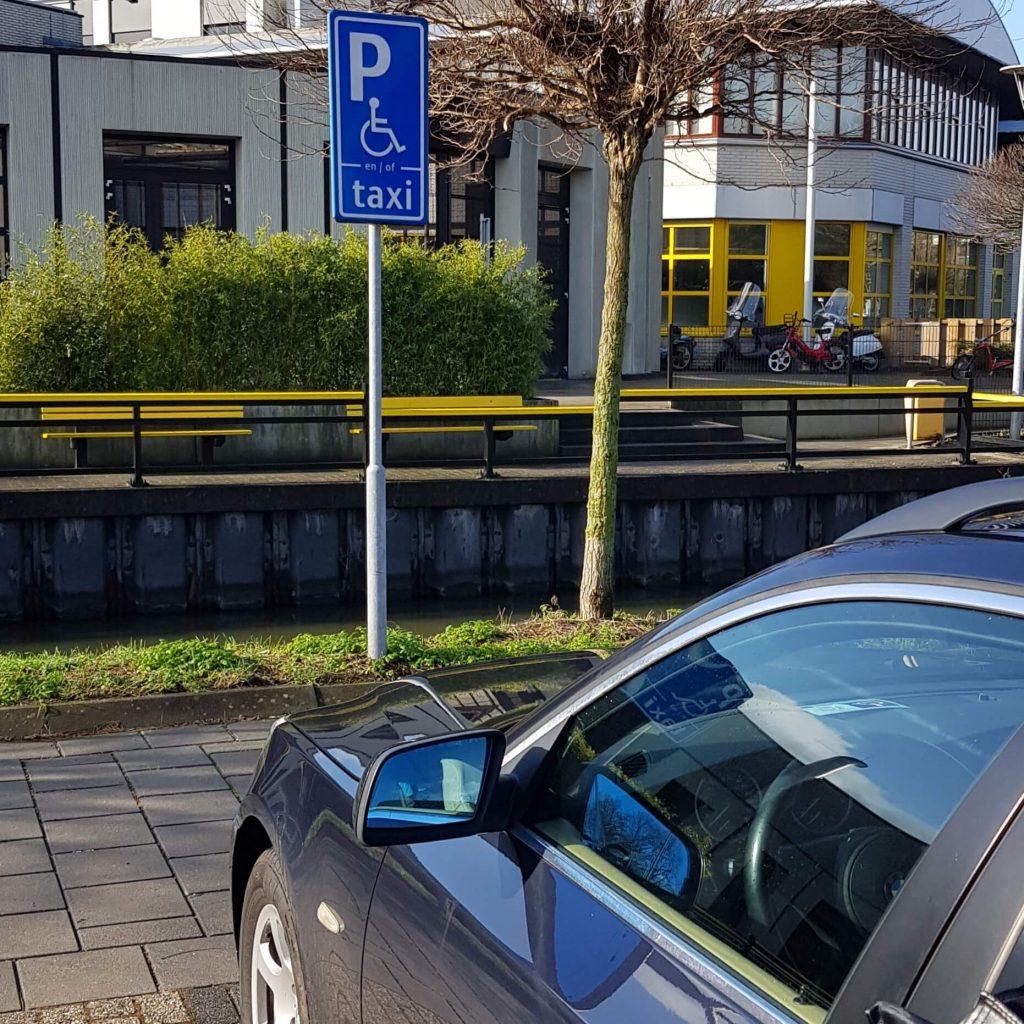 BMW met gehandicaptenparkeerkaart op gehandicaptenparkeerplek bij revalidatiecentrum De Hoogstraat