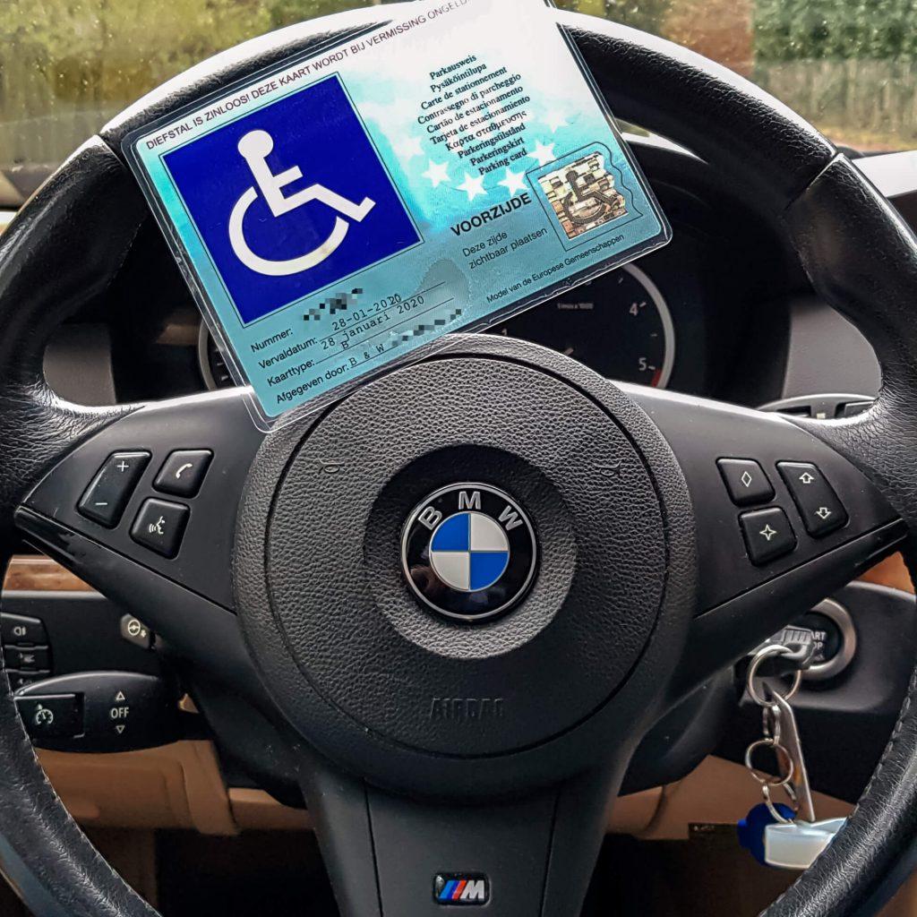Gehandicaptenparkeerkaart vanwege ziekte van bechterew reuma op het stuur van een BMW 5-serie