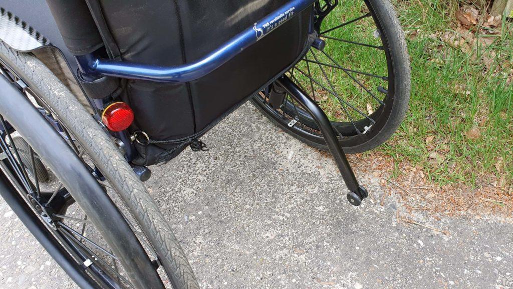 Afbeelding van een antikiepwieltje achterop een rolstoel zodat je niet achterover kan klappen bij het maken van een wheelie