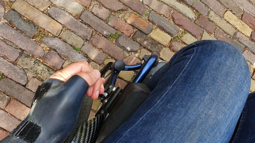 Afbeelding van een hand met spalk of brace die de uitgeklapte remverlenger bedient om zo de rolstoel van de rem te halen