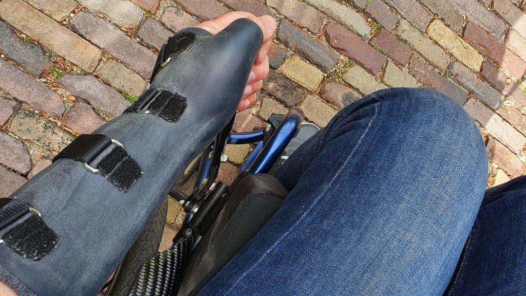 Afbeelding van een hand met spalk of brace die de uitgeklapte remverlenger bedient om de rolstoel op de rem te zetten of van de rem te halen