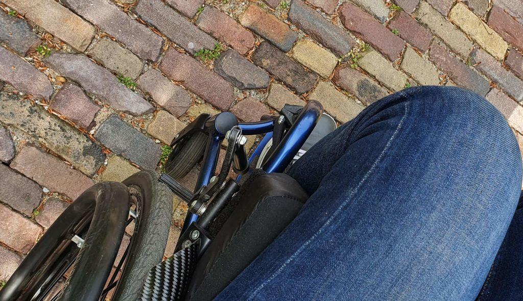 Afbeelding van een rolstoel met ingeklapte remverlengers op de remmen