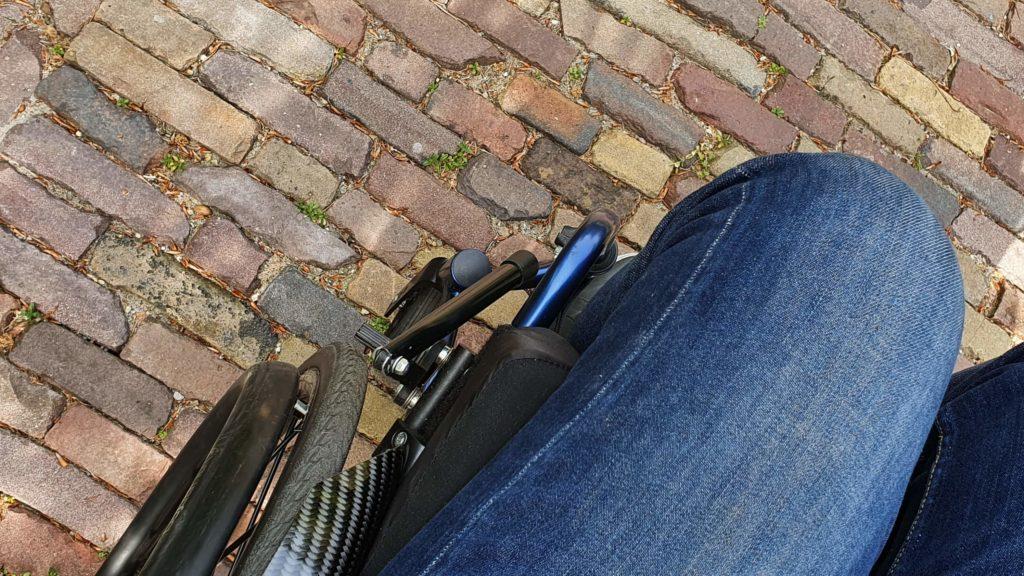 Afbeelding van een rolstoel met remverlengers die na het van de rem te zijn gehaald vrij kan rollen