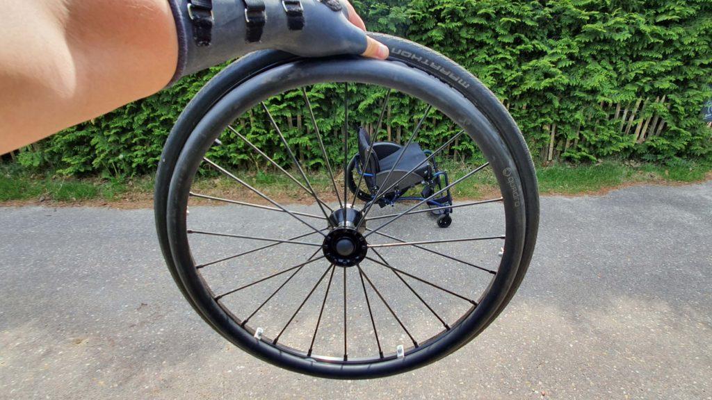Afbeelding van een doorkijkje door een van de spinergy rolstoelwielen richting de TNS Notos roelstoel die dus een rolstoelwiel mist