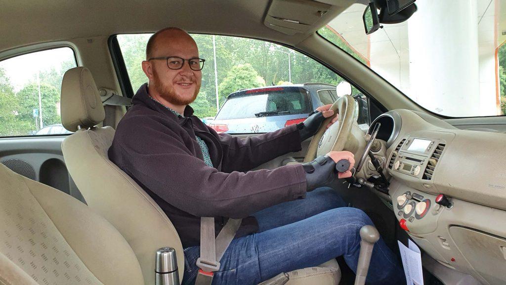 foto van Ralph Stoove achter het stuur van een Nissan Micra met auto-aanpassingen zoals handbediening als proefles autorijden met een beperking of handicap