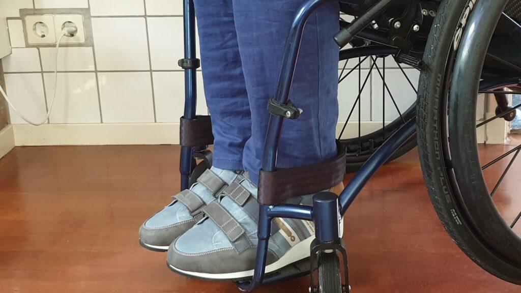 foto van de hoge orthopedische schoenen met klittenband in de rolstoel van TNS