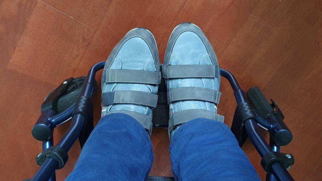 afbeelding van blauwe orthopedische schoenen met klittenband in blauwe rolstoel van TNS Notos
