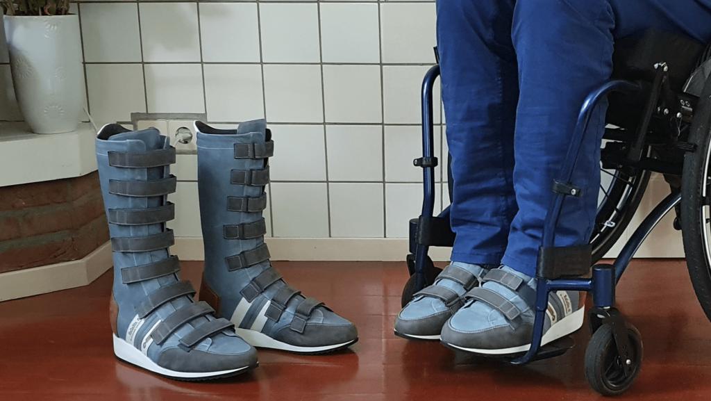 Foto van hoge orthopedische schoenen met klittenband en artrodesekoker en rolestoel met logo van RaGaSto