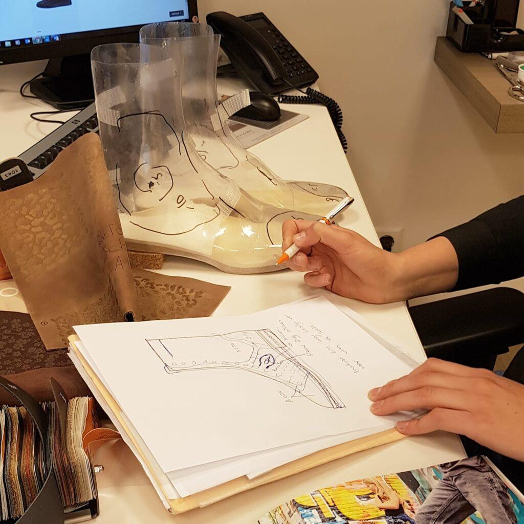 foto van hoe orthopedische schoenen ontworpen worden aan de hand van geheel eigen creatieve ideeën met op de achtergrond folieschoenen of passchoenen en staaltjes leer.
