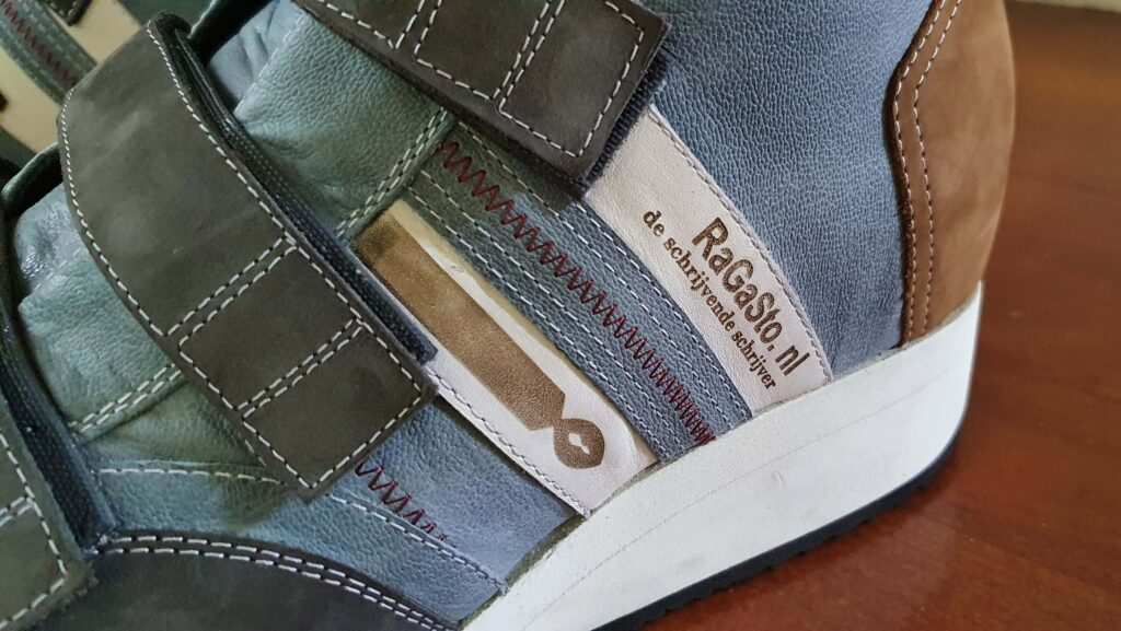 detail van het gebrande logo met website en blognaam RaGaSto op orthopedische schoen met klittenband
