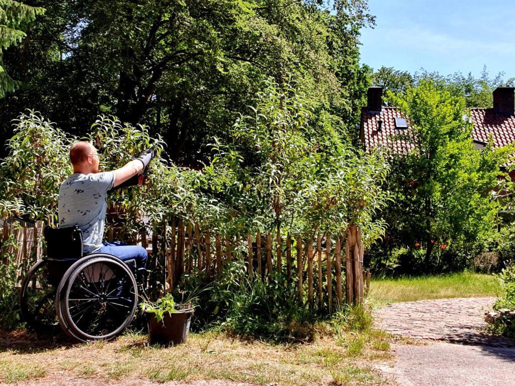 foto van een man in een rolstoel die een heg aan het snoeien is