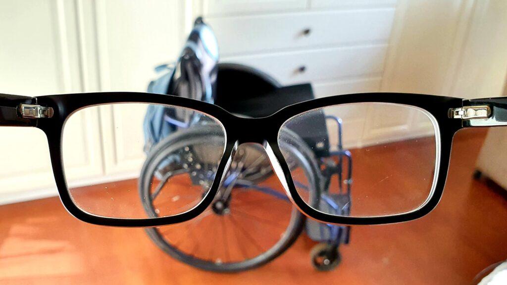 foto van een TNS Notos rolstoel genomen door een bril heen, als illustratie van rolstoelgebruiker versus brilgebruiker