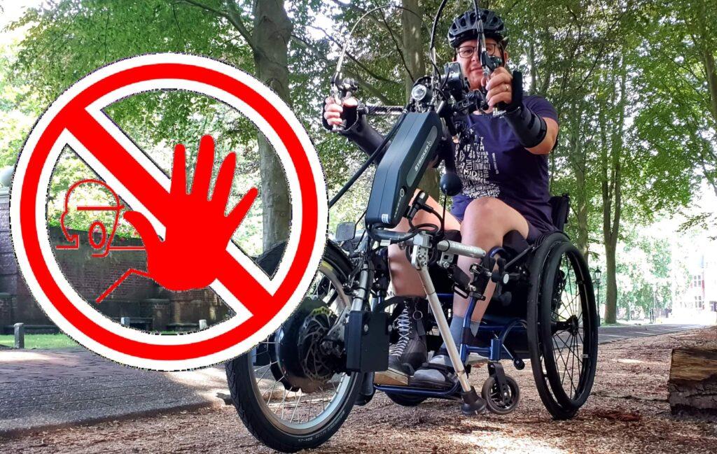 Foto van een rolstoelgebruiker die aan handbiken doet met daarbij een symbool van verboden toegang waarbij het verbod extra geaccentueerd wordt door een handgebaar dat stop uitbeeldt