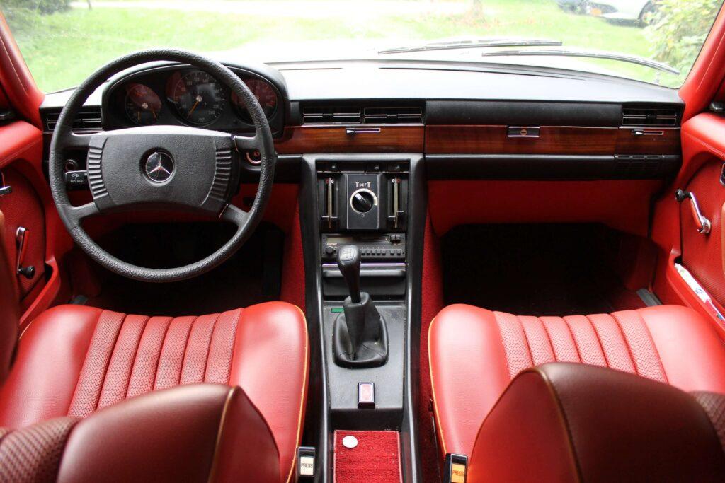 Afbeelding van rood interieur van een Mercedes-Benz W116 280SE uit 1974, waarbij de witte motorkap nog net te zien is.