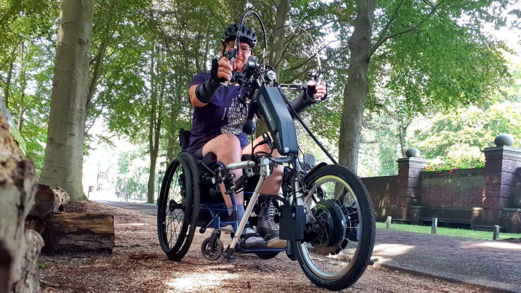 Afbeelding van Ralph Stoové poserend met zijn Stricker Neodrives aankoppel handbike aan zijn rolstoel bij Kasteel De Essenburgh