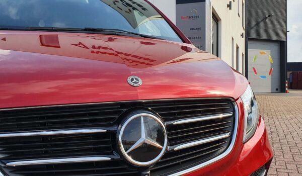 Voorkant van een rode Mercedes-Benz V-Klasse met op de achtergrond het pand met logo van Fleetaccess alarmsystemen