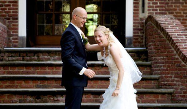Foto van een bruidspaar waarvan links de bruidegom Ralph Stoove die een grap maakt en waar de bruid Marjolein keihard om moet lachen, ter illustratie van het verschil met een misplaatste grap door een trouw- of rouwfotograaf